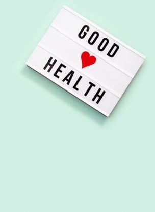 Healthcare and medical concept. Lightbox with words Good Health on mint colored background. Health wishes. Top view.