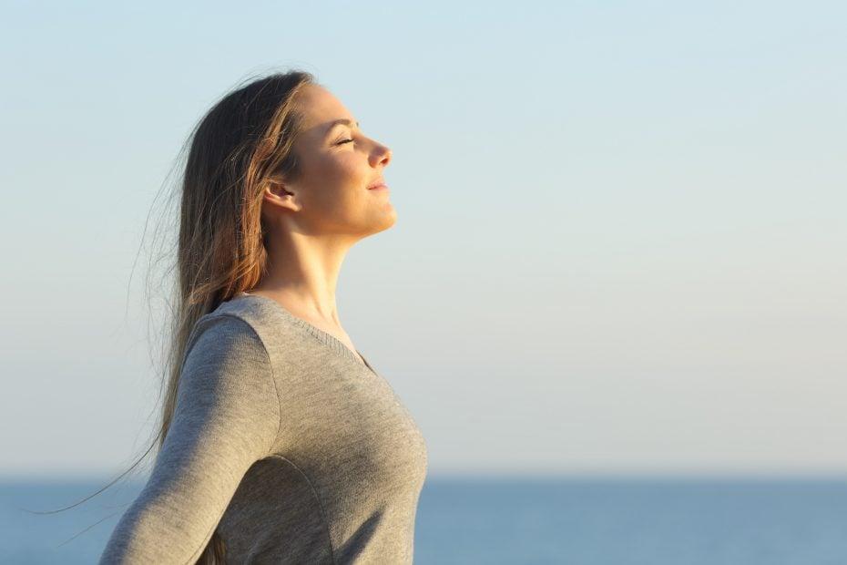 Woman breaths fresh air on the beach.