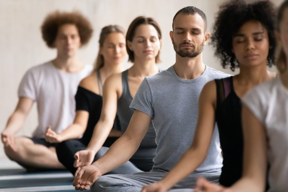 Group of diverse people meditating together visualizing during yoga morning session, focus on Caucasian man seated cross-legged in row with associates, no stress, spiritual practise, lifestyle concept