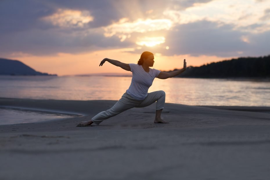 woman doing Tai Chi chuan at sunset on the beach.  solo outdoor activities. Social Distancing. Healthy lifestyle  concept.