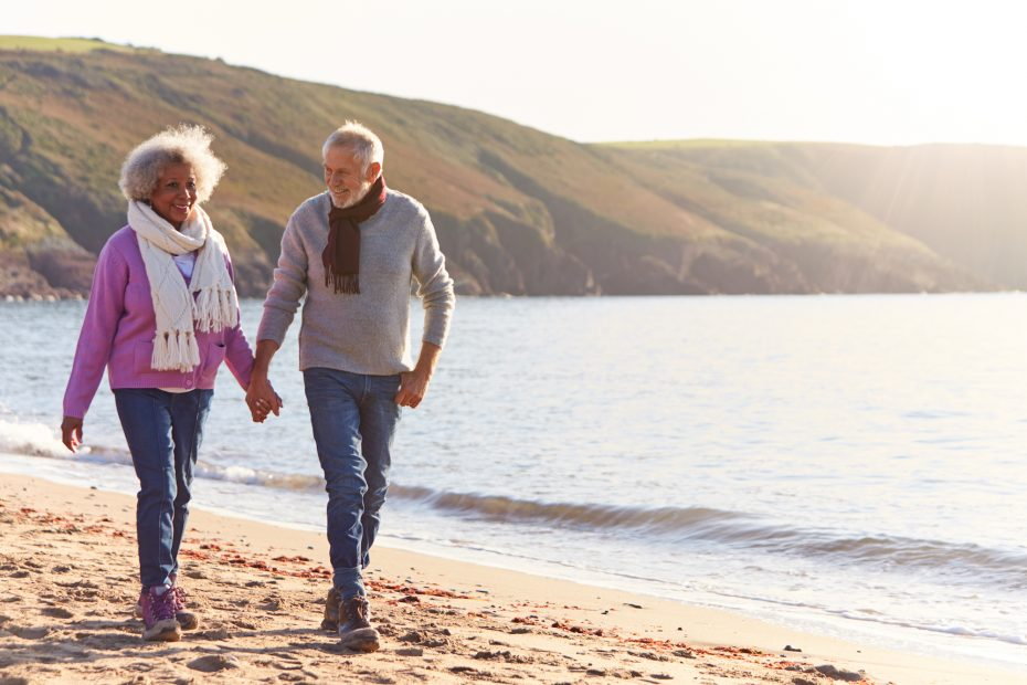 Loving Retired Couple Holding Hands As They Walk Along Shoreline On Winter Beach Vacation.