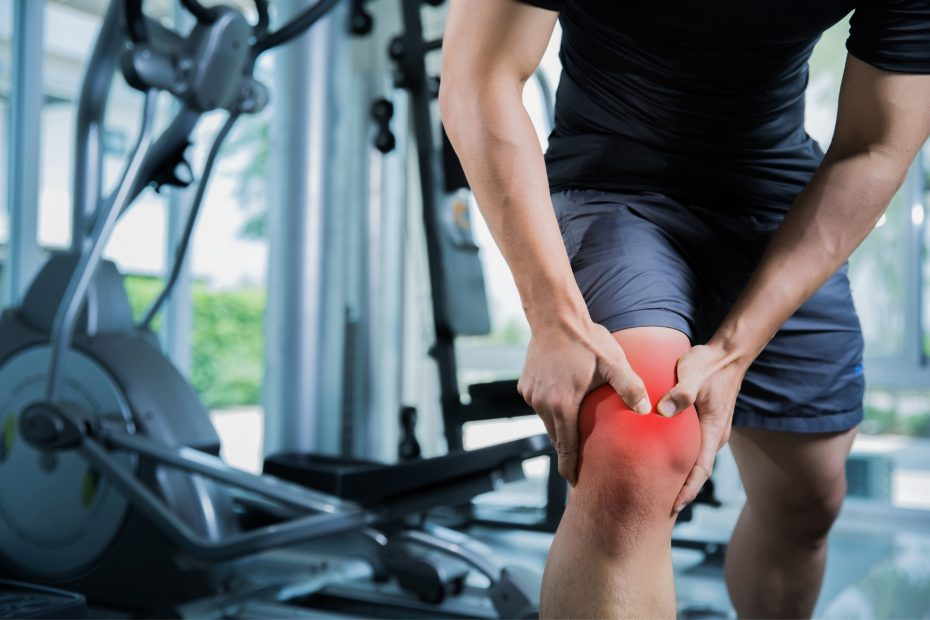 A man in a gym holding his knee.