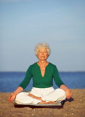 A senior woman sitting on a beach doing qigong.
