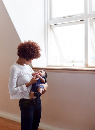 A black woman holding her baby.