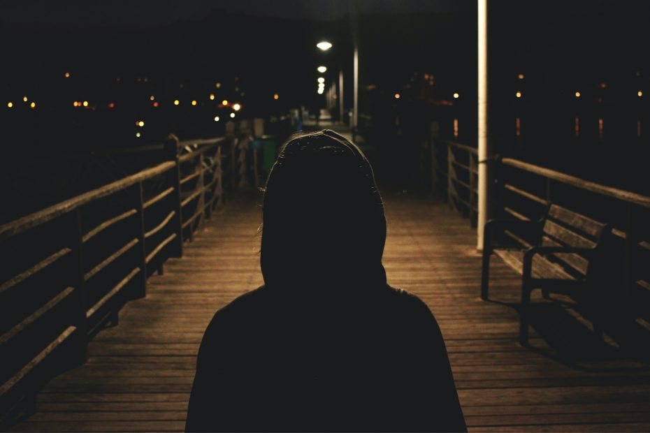 A person wearing a hoodie in the dark.
