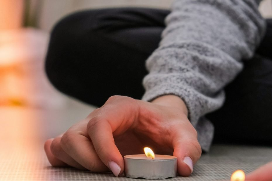 A person lighting a meditation candle.