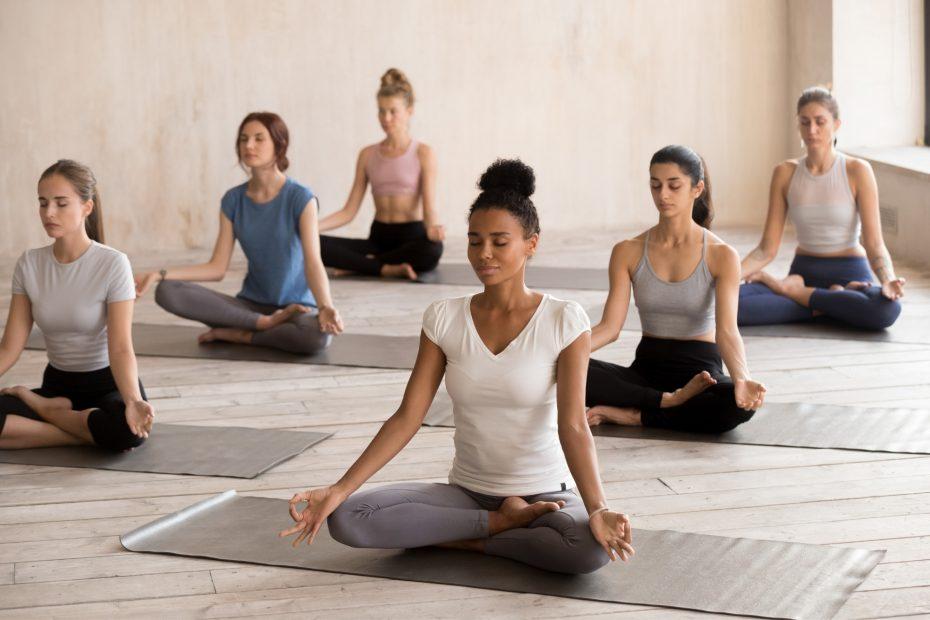 A yoga class sitting in meditation.