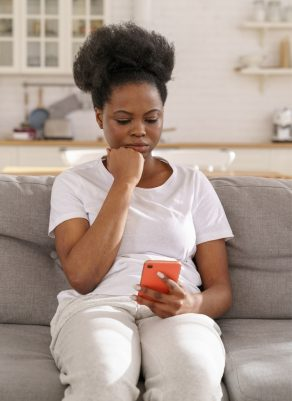 A black woman looking down at her cell phone.