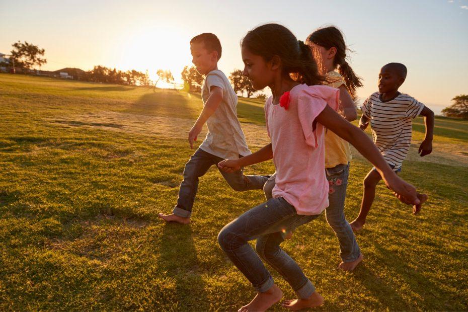Four children running barefoot in a park.
