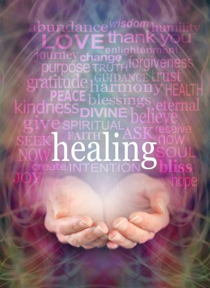 Female cupped hands with the word 'healing' floating above surrounded by a word cloud of healing related words on a swirling misty energy background.