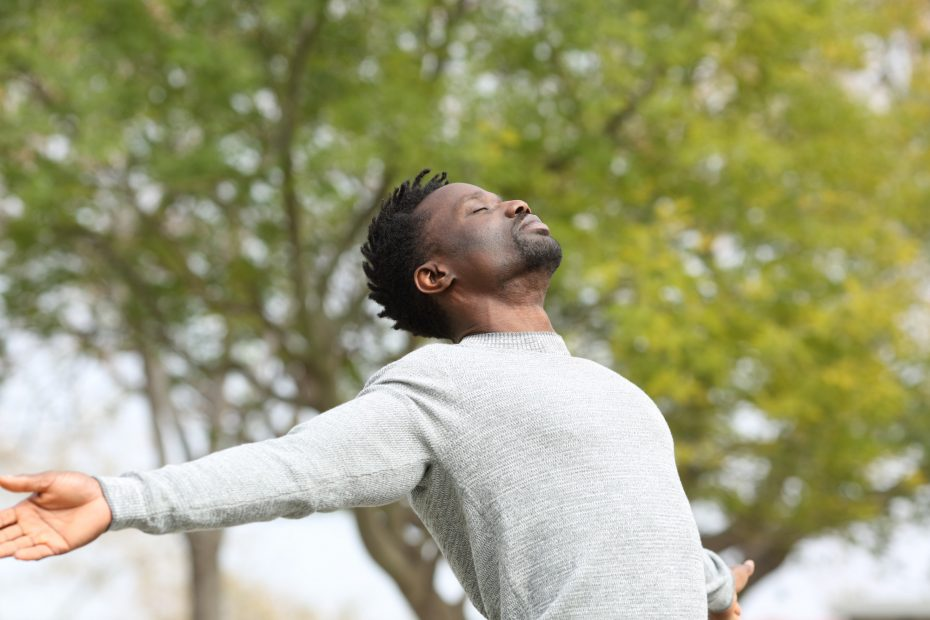 Black man breathing fresh air stretching arms in a park.