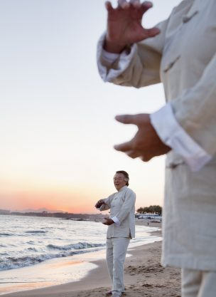 Two older people practicing Qigong on the beach at sunset, close up on hands