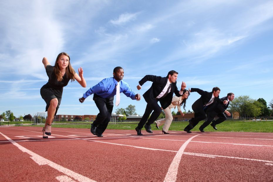 Group of people dressed in business attire racing on track.  Some slight motion blur on people.