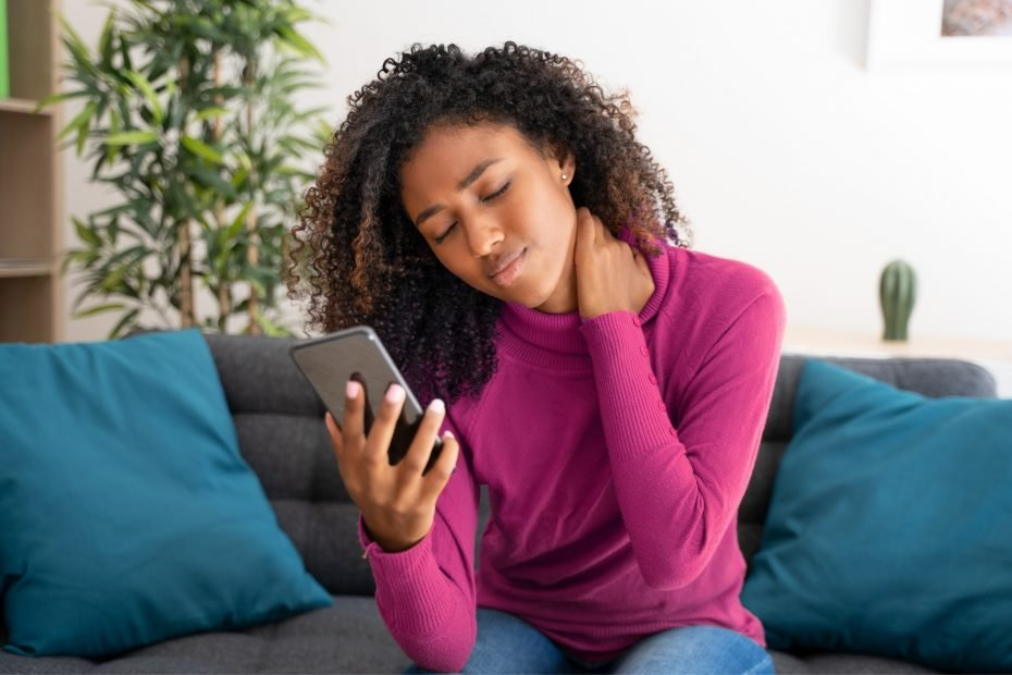 Portrait of black woman feeling neck pain using cellphone.