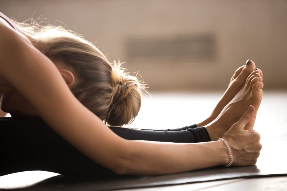 Yogi woman practicing yoga lesson, doing paschimottanasana exercise, Seated forward bend pose, working out, indoor close up. Well being, wellness concept.