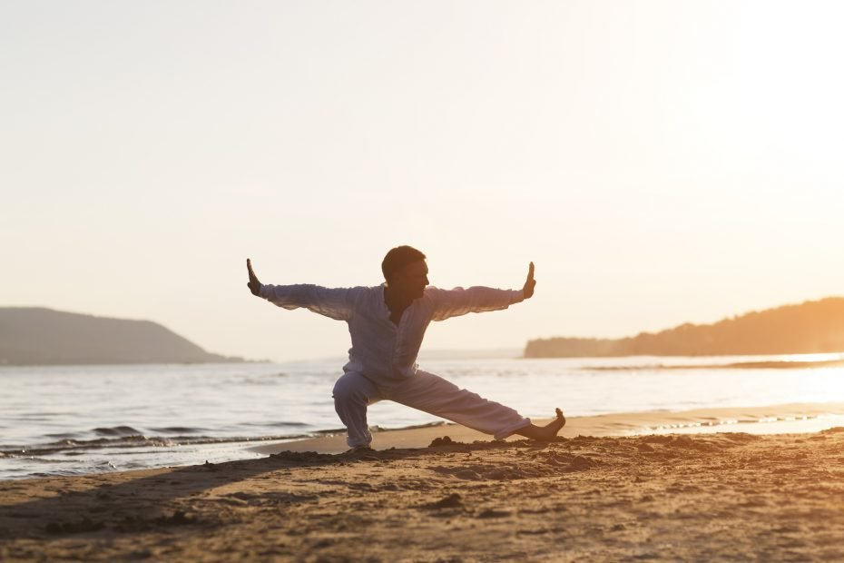 man praticing tai chi chuan at sunset on the beach. Chinese management skill Qi's energy. solo outdoor activities. Social Distancing.