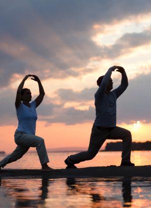 2 people on a beach doing a morning qigong program.